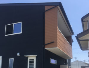 注文住宅のバルコニー|ダーク系の外壁にウッド調パネルのアクセントが映える画像