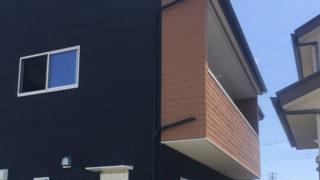 注文住宅のバルコニー ダーク系の外壁にウッド調パネルのアクセントが映える画像
